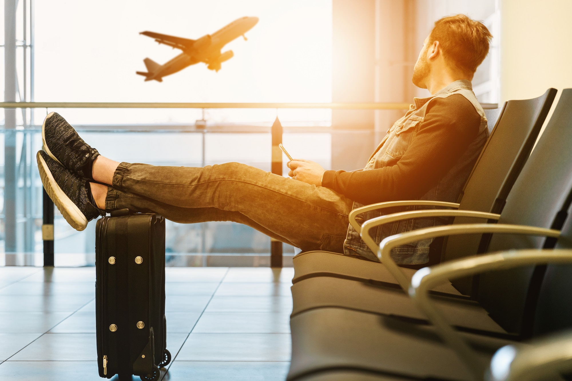man sitting on gang chair with feet on luggage looking at airplane ready to go with travel health
